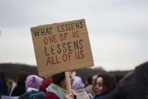"women holding up sign that says ""what lessens one of us lessens all of us"""