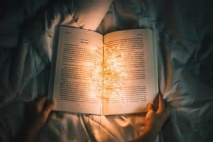 person holding open a book with string lights in the middle