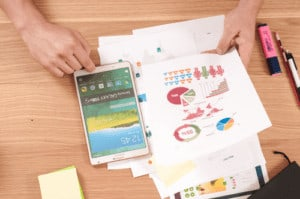 graph papers on table, person holding phone on calculator app