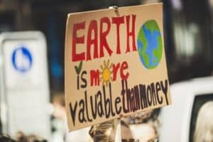 """person holding sign that says """"Earth is more valuable than money"""""""