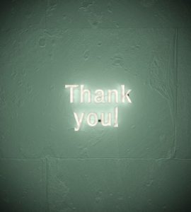 Thank you sign lit up in the middle of a green wall