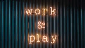 "lit up sign on wall that says ""Work & Play"""