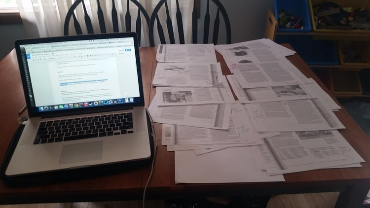 a laptop open with google docs and papers on a table