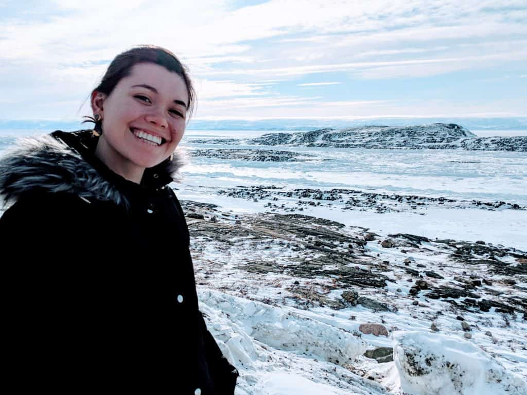 Danielle Moore in front of a beautiful winter landscape
