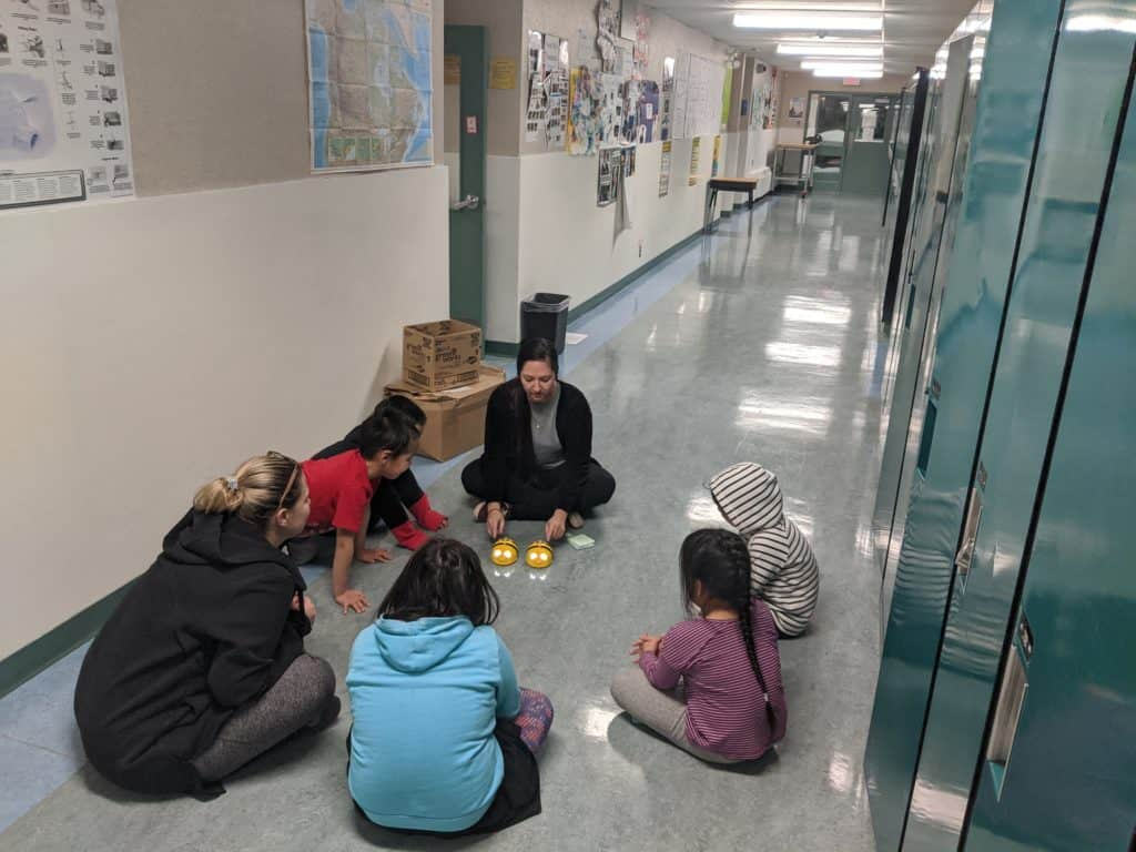 Delivery team Courtney and a teacher playing with beebots in the hall of a school