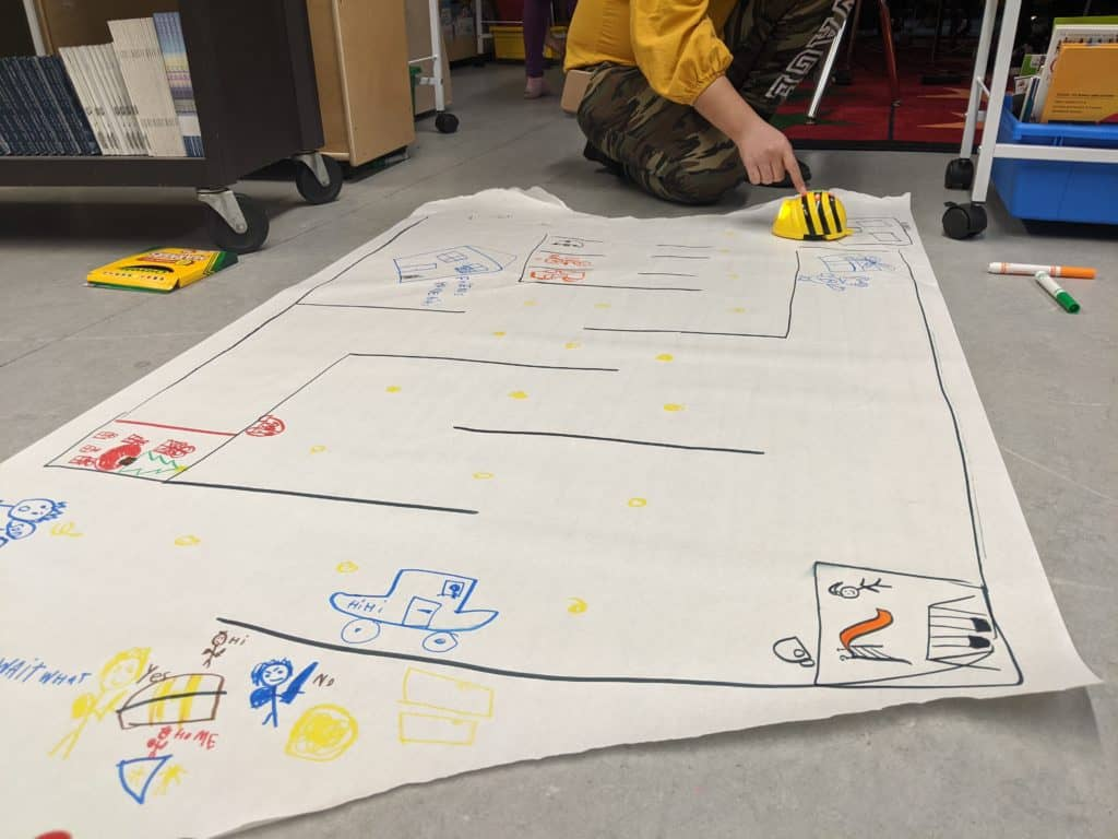 students playing with beebots on a drawn out map