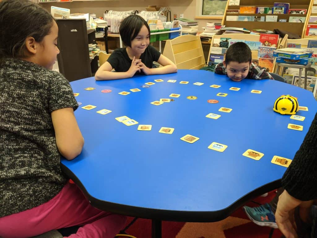 some students gathered around a table playing beebots.