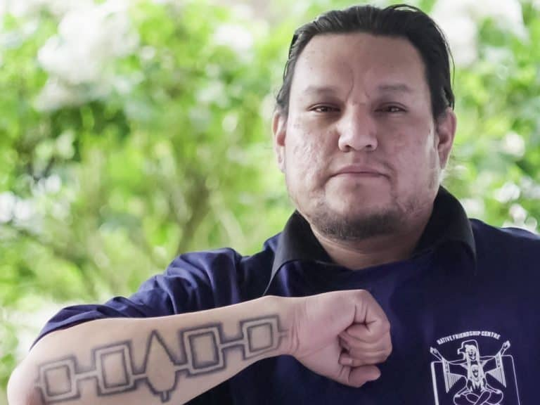 Indigenous man with tattoo on his forearm