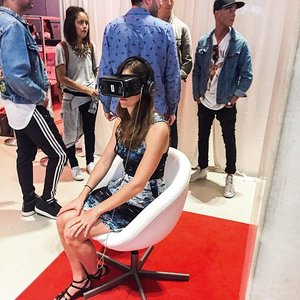 A lady sitting in a white chair with a VR headset on