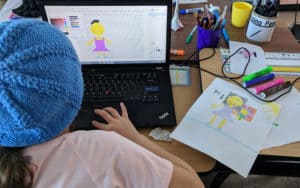 A student creating digital pixel art of a person based on a drawing.