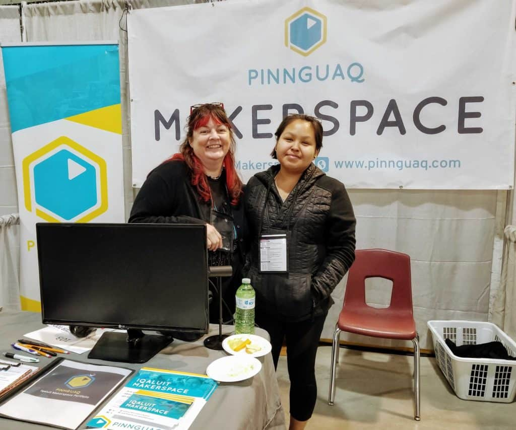Gail and Talia standing in front of makerspace banner at a convention