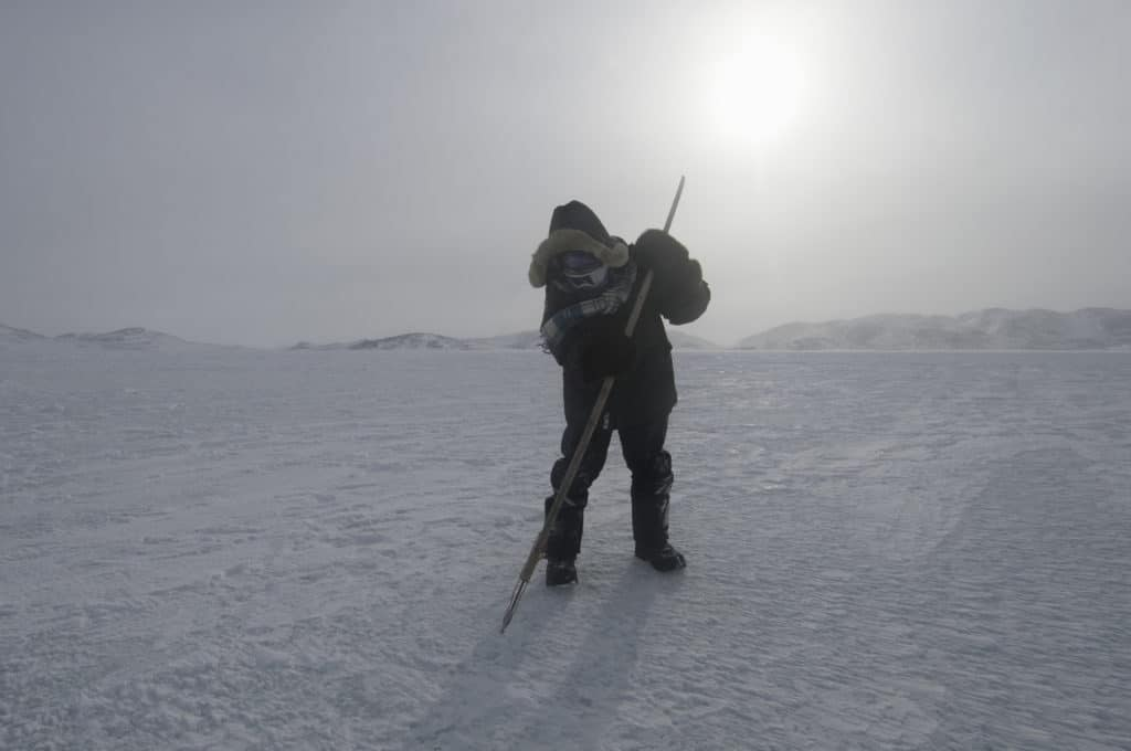 Noah Noggasak demonstrates traditional use of a harpoon to gauge sea ice safety.