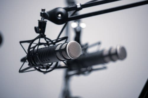 podcasting- two microphones hanging from a pole facing the camera