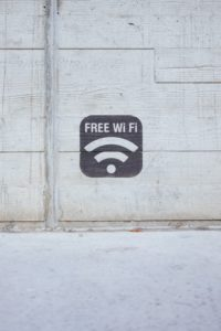 free wifi symbol in the middle of a white a brick wall