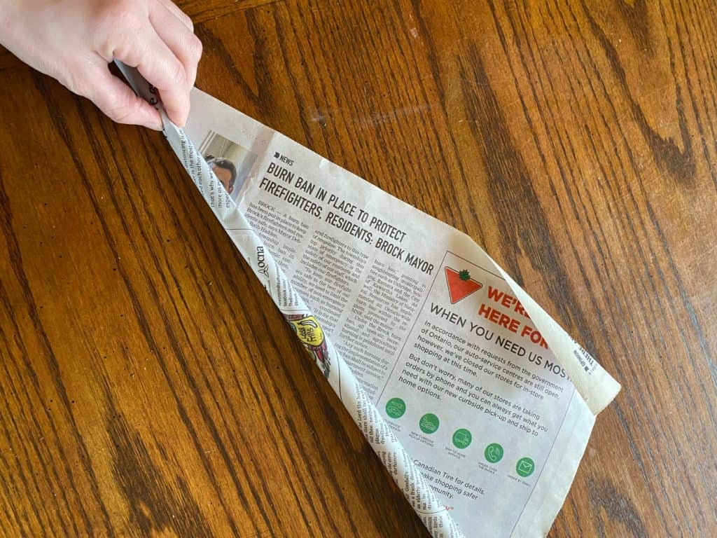 A single sheet of newspaper being tightly rolled.