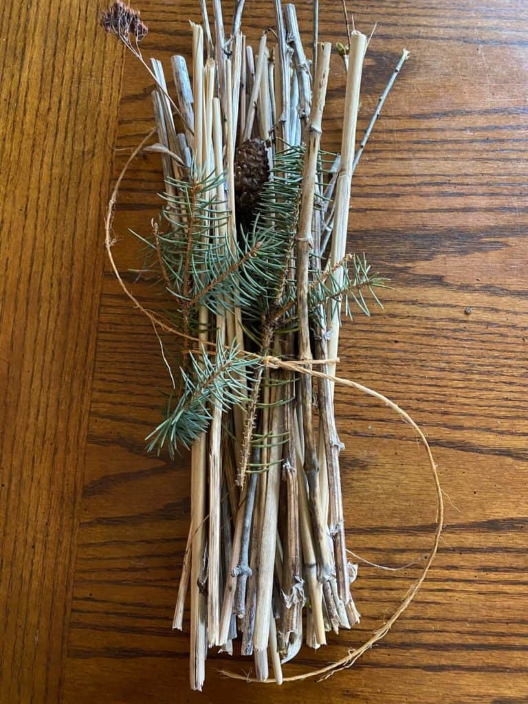 A piece of twine wrapped and tied around the natural materials.