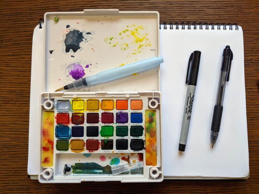 A blank piece of paper with a watercolor paint set and brush.