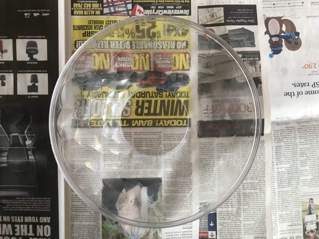 clear bowl sitting on newspaper