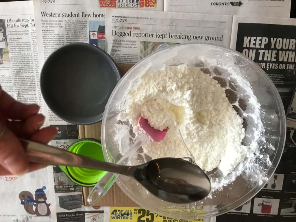 water being added into cornstarch on clear bowl on top of newspaper