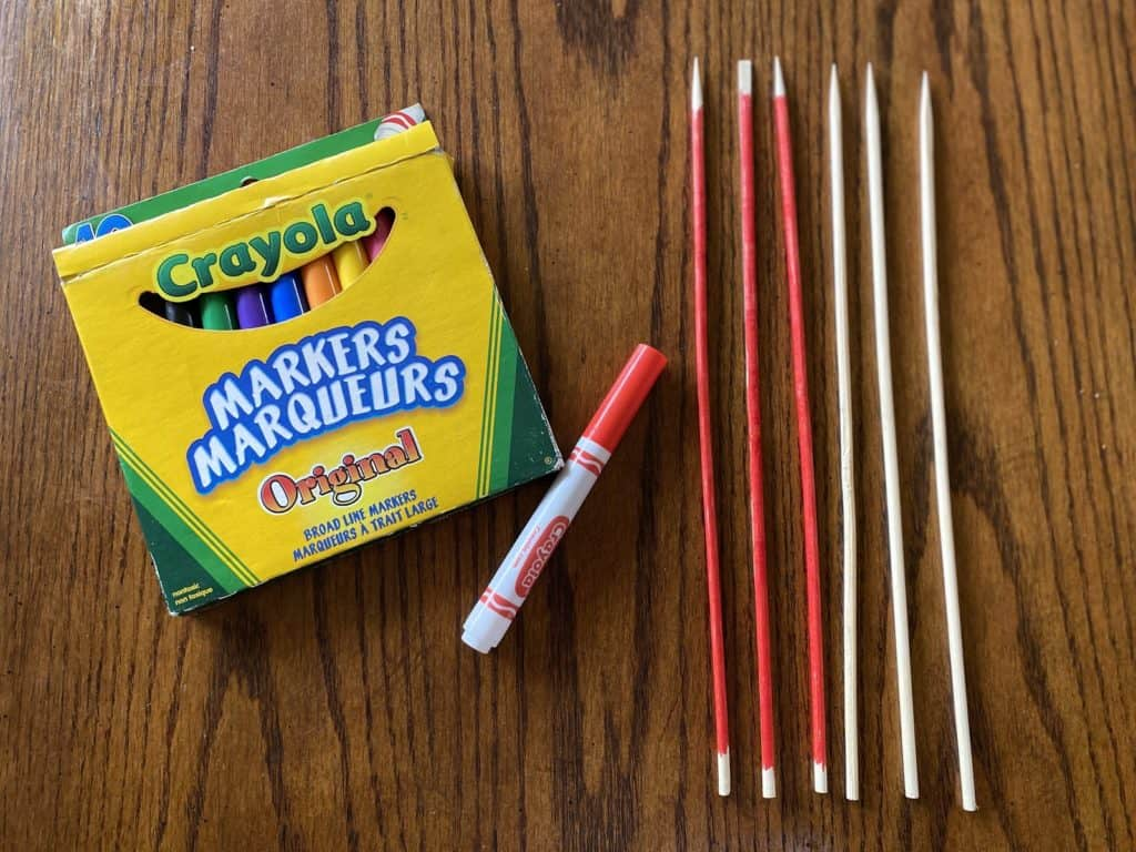 crayola markers laying beside coloured sticks on a wooden table
