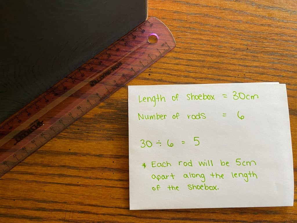 A sheet of paper with information on it laying beside a ruler