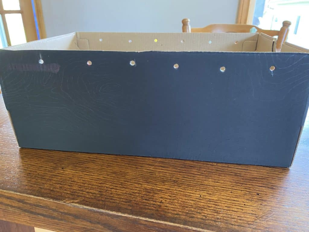 a black box with holds cut into it along the top