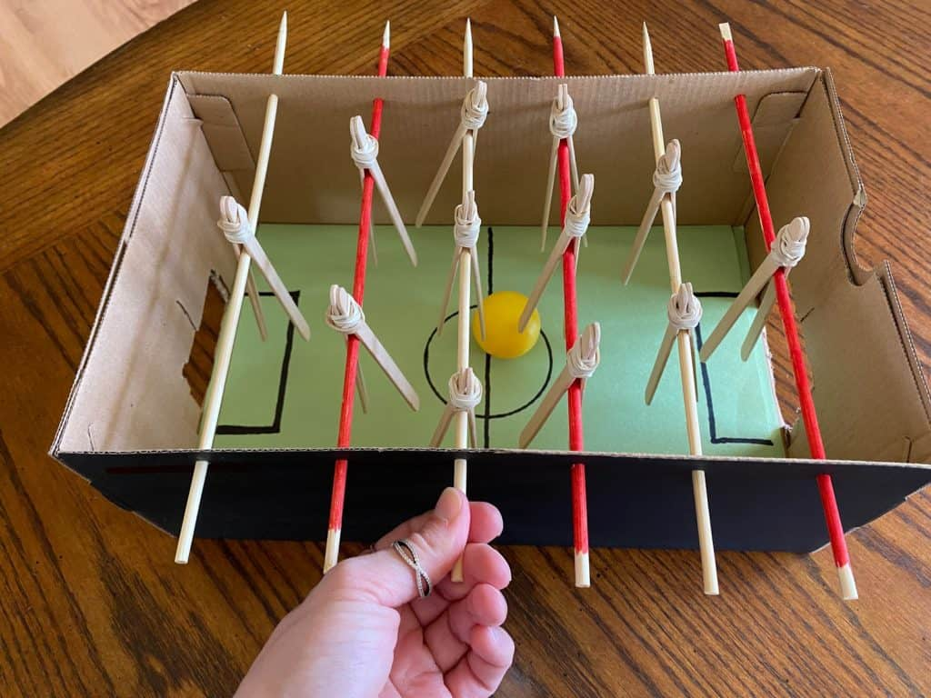 a person playing foosball with a homemade foosball game