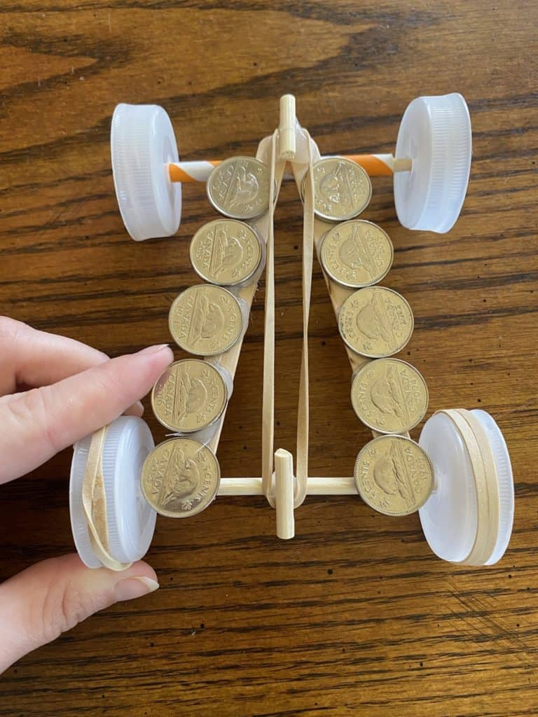 a rubber band hooked around the top and bottom of a DIY race car
