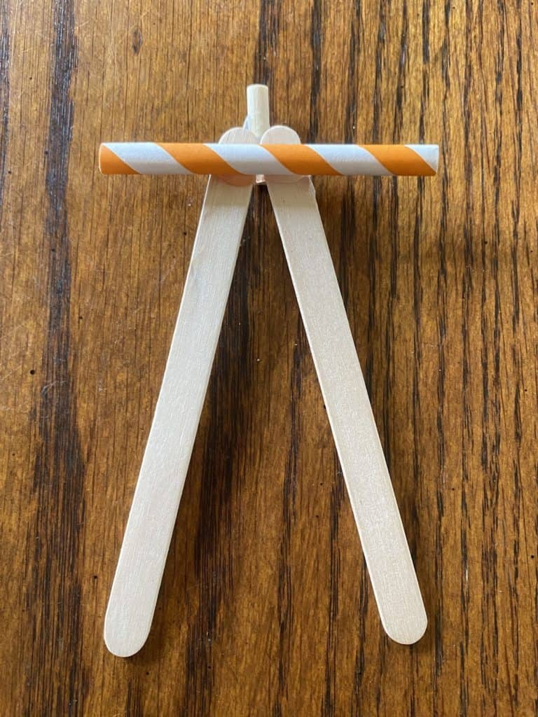 a short orange and white stripped straw laying across two popsicle sticks