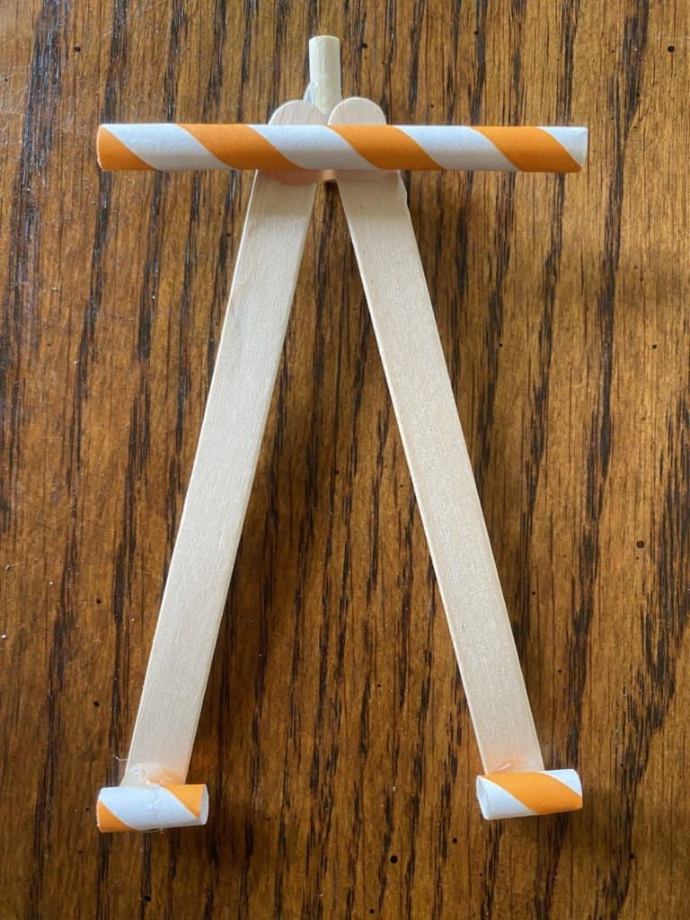 orange and white straws laying across the top and bottom of two popsicle sticks