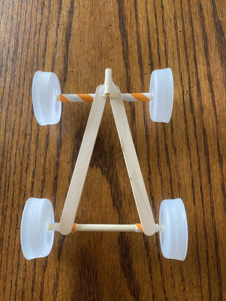 a race car made out of bottle caps, popsicle sticks, and straws