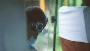 Person wearing mask on public transit, using their phone and wearing headphones.