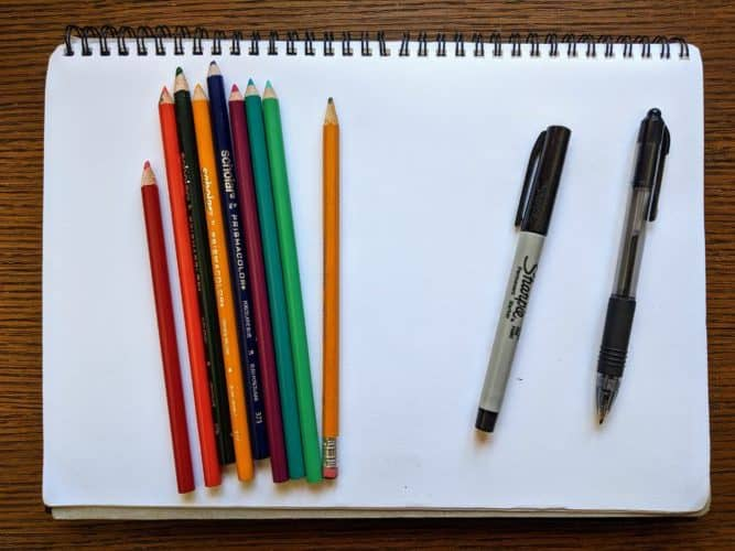 A blank piece of paper with pencil crayons, as well as a marker and pen.