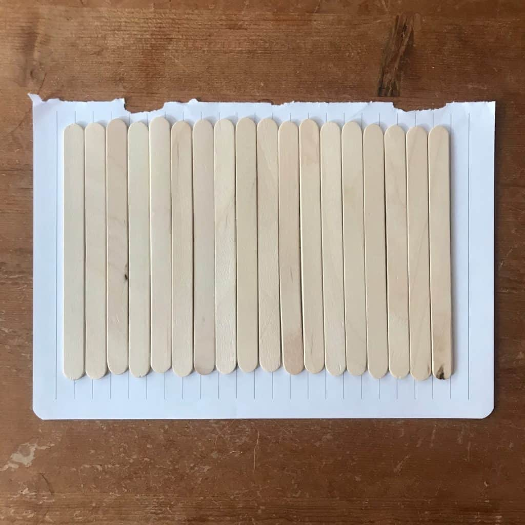 popsicle sticks lined on a lined piece of paper for stick puzzler