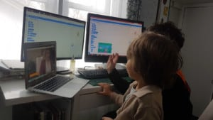 2 learners sitting in front of double monitors, with Google meetings opened on a separate laptop.