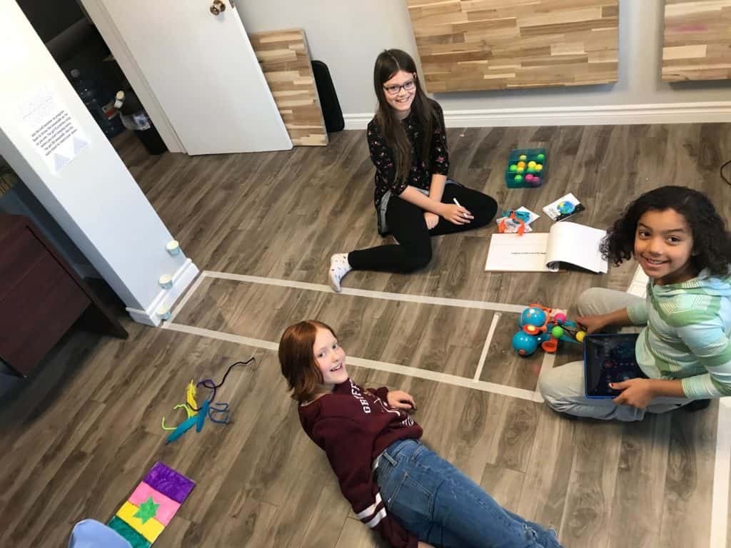 Three students sitting on the floor of the Lindsay Makerspace using a Dash and Dot robot.