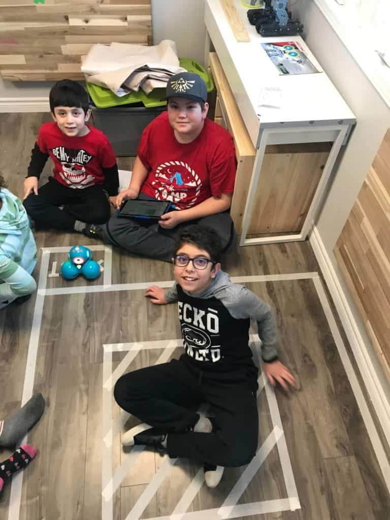 Students sitting on the floor of the Lindsay Makerspace in an obstacle course and a Dash and Dot robot.