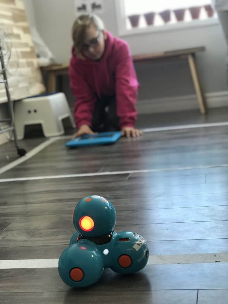 A Dash and Dot robot in main focus, with a student sitting on the floor with a tablet in the distance.