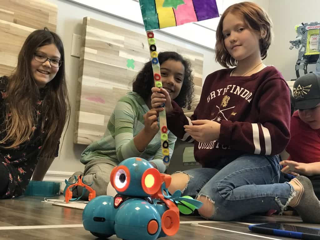 Students sitting on the floor with Dash and Dot robots in the Lindsay Makerspace, holding up a handmade flag.