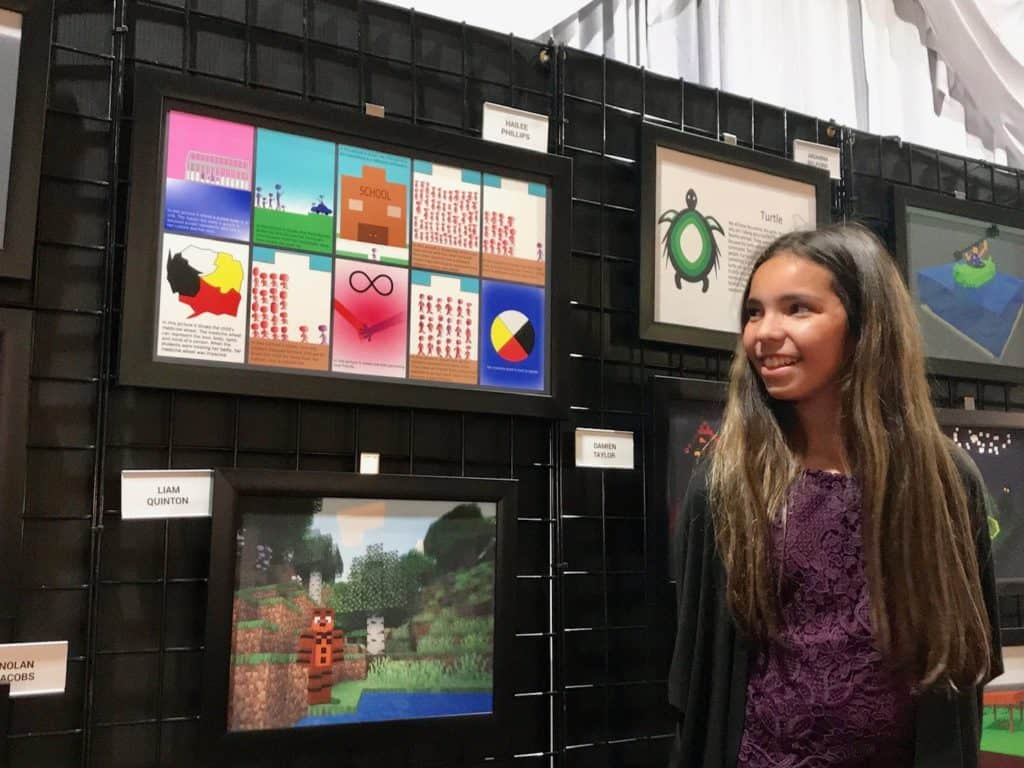 student standing in front of artwork