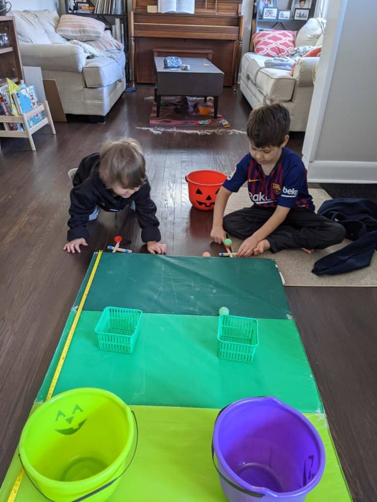 Two kids sitting in front of a green mat, using popsicle sticks to play a game.