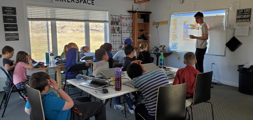A classroom of students looking towards a whiteboard where staff member Mac Pavia is teaching.
