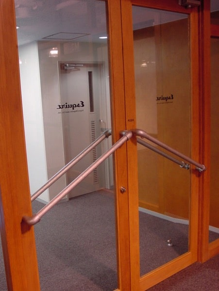 Two glass doors with a wooden frame, in an office building presumably,