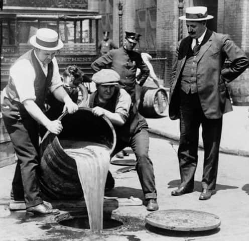 Men dumping alcohol from a barrel into the sewer during prohibition