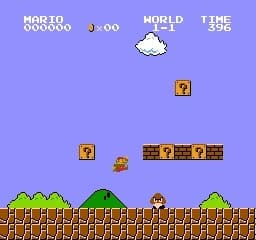 Level 1-1 of Super Mario Brothers with bricks and questions blocks and Mario jumping up to avoid a Goomba
