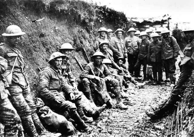 Men sitting in trenches, presumably at war.
