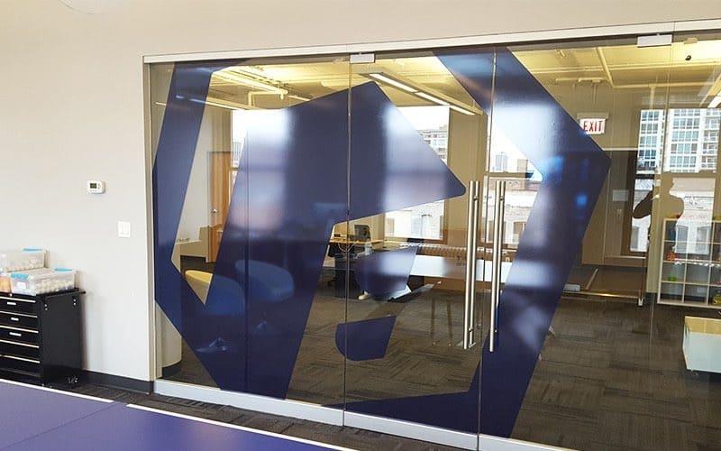 A business logo in dark purple on glass office doors