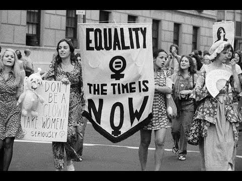 Women holding up protest sign to fight for their rights in the 60s and 70s