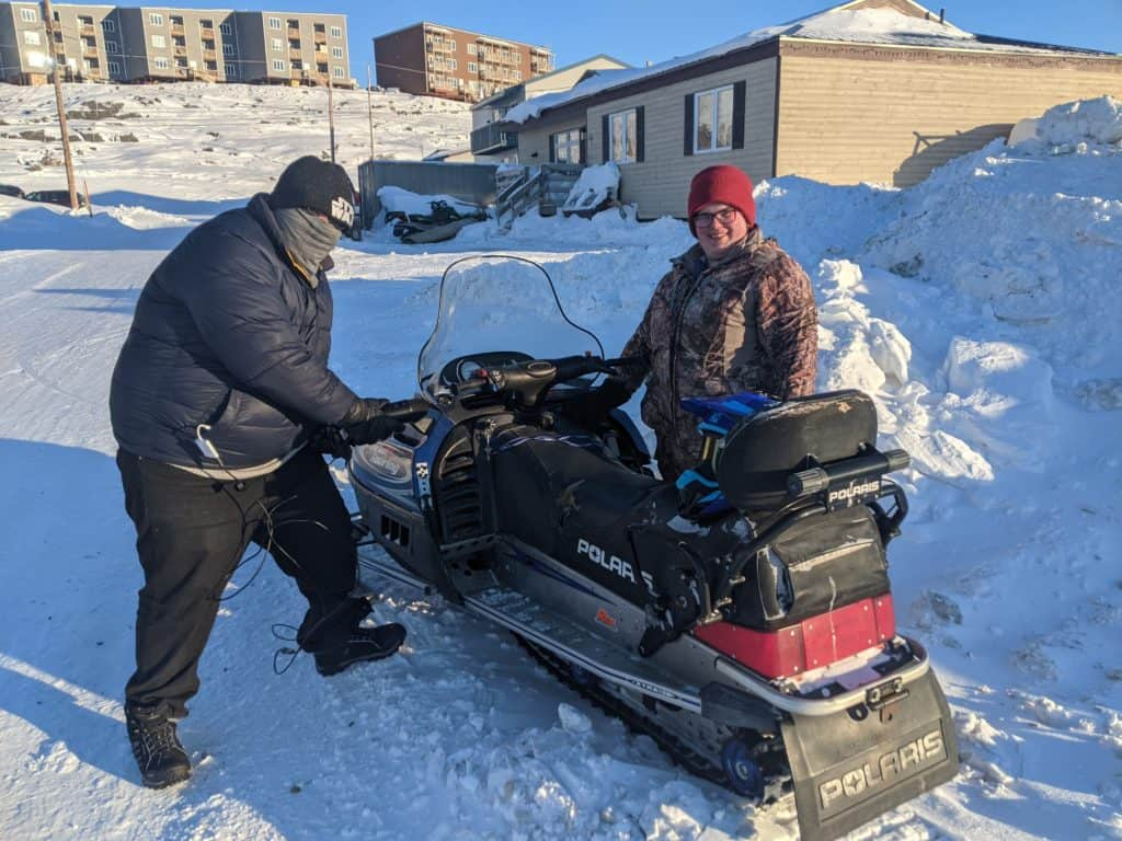 Nunavut Game Jam, two people are shown standing beside a snowmobile.