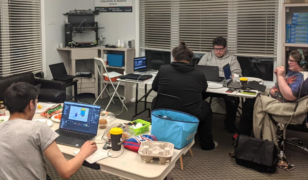Nunavut Game Jam, 4 people are sitting down at 2 tables working on their games.
